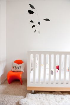 Oeuf classic crib, orange Panton Junior chair, Calder-esque mobile, and sheepskin rug #oeufnyc #classiccrib  https://www.oeufnyc.com/furniture.html