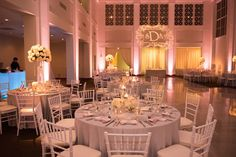 Wedding Reception all White Decor with Chiavari Chairs, Tall Floral Centerpieces and Projection Bride and Groom Initials GOBO and Pink Uplighting | Tampa Wedding Lighting Nature Coast Entertainment Services | Tampa Wedding Venue The Vault | Tampa Wedding Planner Special Moments