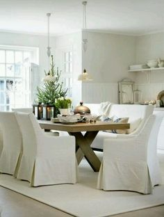 White interior... dining with slip covered chairs and bench, retro pendant light fixtures and raw wood harvest table.