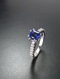 Sapphire solitaire with diamond band.  Cushion cut blue sapphire with diamond band. Custom created at Redford Jewelers in Salt Lake City, UT