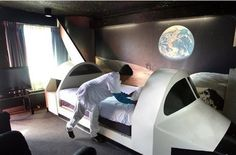 Hostels most universe temperament, the United States, Florida, a waiter in finishing the space shuttle hotel beds, hotel bed in shape is a space shuttle on the wall depicting the vast universe, so travelers have landed in a feeling of space.