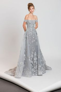 Off-the-shoulder silver evening dress with an overskirt, embellished with floral embroideries.