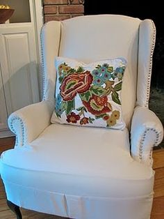 Great DIY idea for a wing chair.  White slipcover and upholstery tacks as 'nail-head' trim.