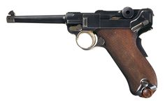 "This is an extremely rare Georg Luger ""GL"" hallmarked prototype DWM Model 1900 Luger. Its 218 serial number indicates that it was made at the same time as the early 1900 Swiss contract guns, but it has a ""reversed"" toggle mechanism design. The purpose of this change was strength for higher velocity ammunition. The center toggle portion has the dished cocking knobs on its rear, with the back toggle's hinge nose extending into the front section, the opposite of the standard toggle…"