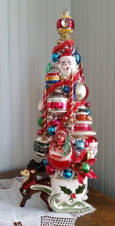 Offering this kitschy vintage reindeer and sleigh that holds a bottle brush tree. Filled with vintage glass ornaments, vintage reflectors and other lovely beads and baubles. Did you see Santa peeking out from the tree? This amazing, one of a kind arrangement measures 18 1/2 tall and 7
