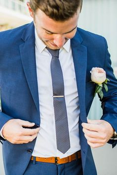 Groom wearing blue suit with patterned tie and blush rose buttonhole | Curly Tree Photography | See more: http://theweddingplaybook.com/elegant-boho-wedding-by-the-beach/