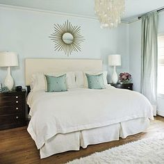 Crisp and Clean | Keeping the basics white gives a clean, versatile look. Hanging a mirror above the headboard reflects light and creates a focal point. | SouthernLiving.com