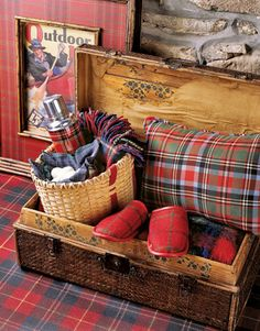 Vintage box filled with a small wicker bag, thermos, a throw, blanket and comfy cozy slippers.