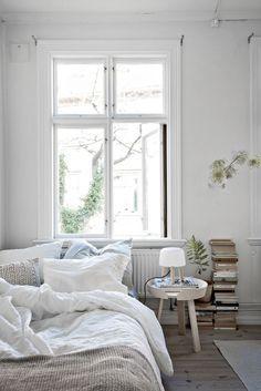 Gemütliches Bett mit Decken und Kissen, kleiner Beistelltisch und Bücherstapel auf dem Boden. #bedroomgoals #Schlafzimmer #bedroom