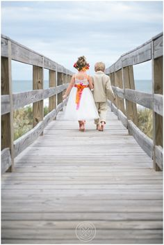 Flower girl and ring bearer walking down the aisle (dock) to the beach wedding