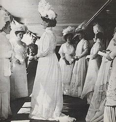 Tsarina Alexandra and her ladies. The blouson look of the early 1900s is gone in this assortment of dresses, putting this in the 1910s. The broad, ornate hats are also from the 1910 era. Two of the Ladies in this photo wear dresses with outer and inner sleeves, all wear long sleeves and hats, and all wear natural waistlines.