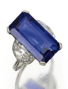 An Art Deco sapphire and diamond ring, Cartier, Paris, circa 1930. The emerald-cut sapphire weighing 15.42 carats, flanked by 2 half-moon-shaped diamonds weighing approximately 3.40 carats, mounted in platinum, size 6, signed Cartier, Paris, numbered. #Cartier #ArtDeco #ring