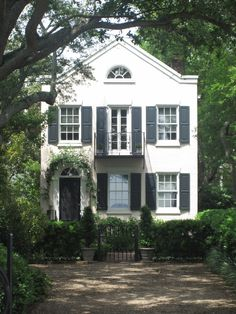 Home with southern charm in the city of Charleston, South Carolina. White clapboard with black shutters.