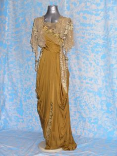 EVENING DRESS (architect 171) (Translated from Italian) 1912 EVENING DRESS FULL, MADE IN MUSTARD COLOR SILK, LACE INSERTS, polychrome silk embroidery, DECORATIONS AND STRING TASSEL. FRONT CLOSURE BY HOOKS.