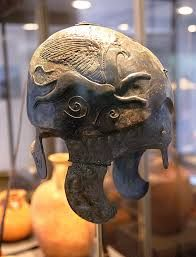 Greek Helmet with a griffin. Found at the gate of the ancient city of Stobi.    Stobi was an ancient town of Paeonia which was, later conquered and subjugated by Philip of the ancient Greek kingdom of Macedon.  It is now part of the Slavic country FYROM.  Slavs began to arrive in the region approx 7th century BC