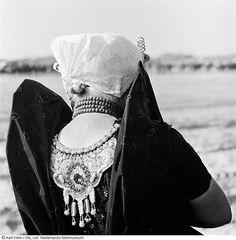 Vrouw in Zeeuws-Vlaanderse klederdracht, op de rug gezien (1962)