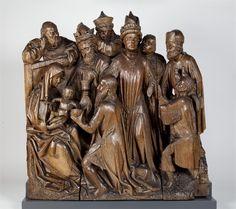Anonymous (Utrecht), Aanbidding der koningen, Links op de voorgrond zit Maria op een stoel met hoge rugleuning, waarvan de zitting is bekleed met een gevlochten stromat. Zij is naar rechts gewend en draagt het naakte Christuskind in beide handen. Met haar rechterhand steunt zij zijn linkerbeen en met haar linkerhand zijn bovenlichaam. De kleine Christus heeft zijn gezicht driekwart naar rechts gewend, waar één van de drie koningen voor hem neerknielt. Catharijneconvent, Utrecht