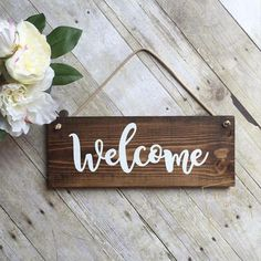 This beautiful Welcome Sign makes the perfect addition to any home and a great housewarming gift! Our Welcome sign- -is stained medium/dark brown -all lettering is painted white -has a clear sealer to ensure quality -measures approximately 14.5 wide by 5.5 inches tall *Wreath is NOT included* Please note that all our sign are made of wood and no two pieces will be the same. Some will have more or less knots, markings, ect. Recommended for use under a covered area if being used outside. All…