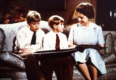 Living history: From left to right, Prince Andrew, Prince Edward and The Queen looking at one of her father's photo albums showing pictures of Elizabeth and Margaret as children.