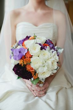Bridal bouquet of white cabbage roses, white dendrobium orchids, purple orchids, orange spray roses, dark purple carnations, silver brunian and dusty miller. Photograph by Theresa Choi.
