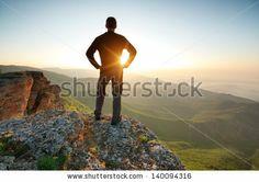 Man on top of mountain. Conceptual scene. by djgis, via Shutterstock
