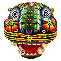NEW! This beautiful, one-of-a-kind beaded jaguar head was made by pressing tiny glass beads into natural beeswax spread over a hand-carved wooden form.  Bead art is made in limited quantities by the Huichol and Tepehuano Indians of southwestern Mexico.  Click here for additional information on the Huichol people and how this art was made, and here for an Adobe Reader file describing the significance of their symbols and color choices.