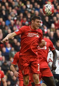 Liverpool's English midfielder James Milner heads the ball clear during the English Premier League football match between Liverpool and Tottenham...
