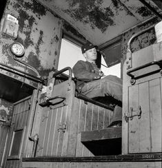 """March 1943. """"Walter V. Dew, rear brakeman, on the Atchison, Topeka & Santa Fe between Chicago and Chillicothe, Illinois, watching the train from the cupola."""" Photo by Jack Delano for the Office of War Information."""