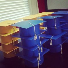 "DIY Preschool graduation caps. 8x8"" THICK cardstock/posterboard for top. 4x21"" strip for bottom. cut 2 inch sections 1"" down along 21"" strip. Staple together, fold down tabs. Glue to top. Tassle uses school colors, wrapped 3 times around 3 fingers with 10"" extra. Tie loops together, snip ends to make tassle. wrap another string around top to hold everything together. Tied to brad and inserted into middle of cap."