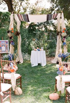 Brides.com: 30 Amazing Ceremony Structures. A boho-inspired chuppah with fall flowers and rustic drapery, created by Bella Raines.