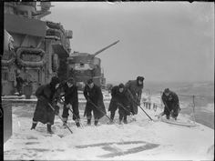 Sailors clearing the decks of snow on board HMS KING GEORGE V whilst she was in Arctic waters. Often the decks were a foot deep in snow. One of her 5.25 inch gun turrets can be seen in the background. Clearing snow from decks was a constant task in Arctic waters. Accumulation added weight and, in extreme case, could affect the ship's seaworthiness.Also, decks full of snow were clear invitations to accidents.