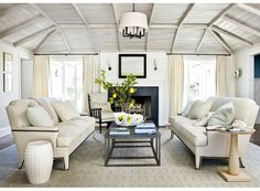 Neutral living room with matching sofas facing each other, beamed whitewashed ceiling
