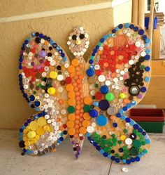 Colorful Butterfly (cut from a piece of scrap plywood) and covered with round plastic recycled caps of all kinds.  Can be hung outside when finished a wall art.  Happy Earth Day, April 22