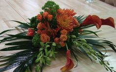 This is an arrangement consisting of dahlias, roses and calla lilies in an orange color scheme.  See our entire selection at www.starflor.com.  To purchase any of our floral selections, as gifts or décor, please call us at 800.520.8999 or visit our e-commerce portal at www.Starbrightnyc.com. This composition of flowers is generally available for same day delivery in New York City (NYC).  C134