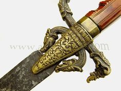 The carving to the lion hilt is finely done with mane, eyes and open jaws all depicted in traditional Sinhalese tradition style, very fine condition and colour to the ivory rich and golden. The metal guard parts are extremely finely chiselled with scrollwork and inlay of bronze and silver, various makarra or lion heads adorn the quillon terminals and a similar larger makarra or bird heads surmounts the flared handguard to the front of the hilt.