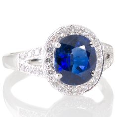 An oval blue unheated sapphire and diamond cluster engagement ring. View our collection of antique, Art Deco, and modern jewellery at www.rutherford.com.au