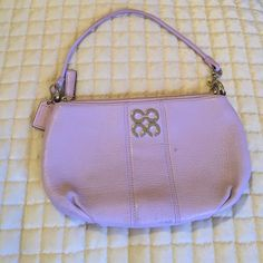 Lilac coach wristlet Lilac colored leather coach wristlet. Has 2 small imperfections pictured. Imperfections are not as noticeable as in pic. The strap can be used as shown, or moved to one side. Approximate size is 9.5 inches by 6 inches Coach Bags Clutches & Wristlets