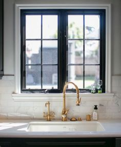 The contrast between the black window frame and brass faucet is stunning.