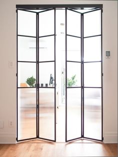Folding steel doors separate the home office from open plan kitchen and living room in Hutchison Flat, Montreal Room Divider Doors, Room Doors, Kitchen Doors, Open Plan Kitchen, Home Door Design, Casa Loft, Types Of Doors, Folding Doors, Steel Doors