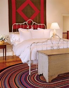 Very nice blend of antique quilt on wall, side table, bed, hooked rug and rustic, antique old paint, 5 board blanket-type chest.