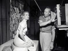 Grace Kelly in the portrait gallery at Paramount Studio in Hollywood is pictured with Bud Fraker, head photographer at Paramount. 1955.