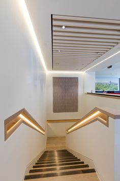 Staircase with lit recessed oak handrail detail.
