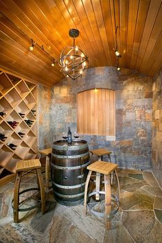 Minimal wine rack for the tasting room with wine barrel table and recycled stools