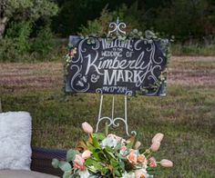 """A chalkboard welcome sign will be accented with a swag of greenery on the top with clusters of blush """"candy bianca"""" roses, light pink """"Esperance"""", blush """"cremet"""" spray roses, and ivory spray roses."""