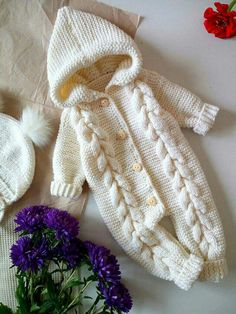 Cabled hooded onesie for baby.