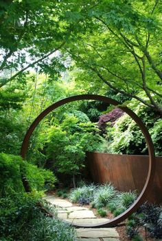 "For a zen influence, divide your garden into two sections by installing a circular opening or ""moongate"" onto a fence or trellis."