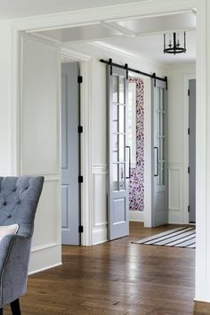 Medium stain oak hardwood floors contrasting with white paneling and blue-grey doors Oak Hardwood Flooring, Laminate Flooring, The Doors, Sliding Doors, Wood Doors, White Paneling, Interior Barn Doors, Interior Walls, Home Office Design