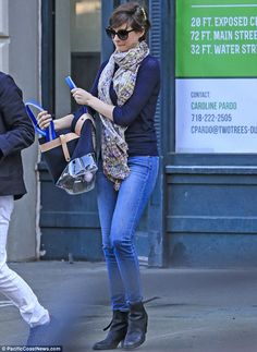 Anne Hathaway wore a navy sweater with jeans and a dark bag