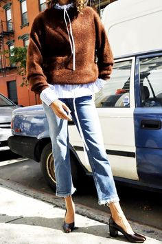 a sweater is worn layered over a striped shirt, paired with frayed-hem jeans and pumps...