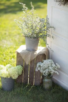bunches of one flower or greenery type in containers has a more relaxed feel for a wedding
